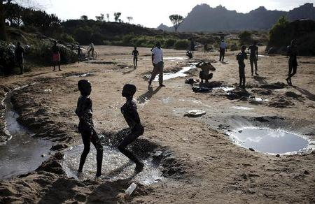 Karamojong tribe boys bath in a dry riverbed in town of Kaabong in Karamoja region