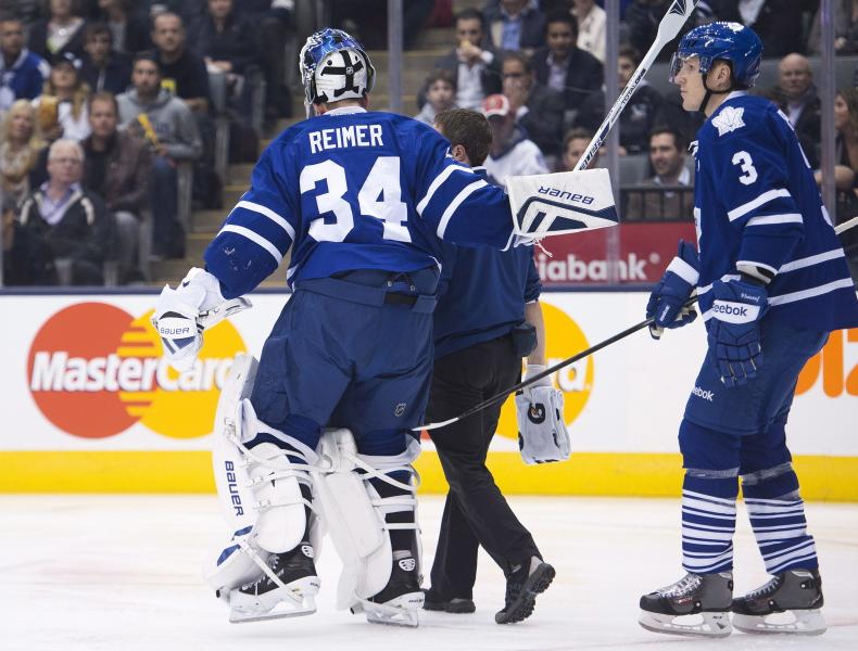 Toronto Maple Leafs goalie James Reimer, left, leaves the game after being injured as Dion Phaneuf, right, trails, during the first period of an NHL hockey game against the Carolina Hurricanes in Toronto on Thursday, Oct. 17, 2013. (AP Photo/The Canadian Press, Nathan Denette)