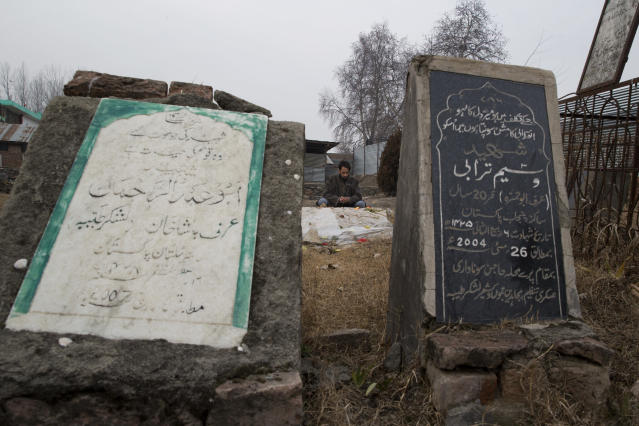 In this Dec. 26, 2018, photo, Asim Aijaz prays near the grave of his nephew Saqib Bilal Sheikh, who was 16-years-old when he died in a gunbattle, at martyrs graveyard in Hajin village, north of Srinagar, Indian controlled Kashmir. On a hot day in August, two teenage boys in the Kashmiri town of Hajin, including Saqib, walked away from a local soccer pitch, only to return home months later in body bags. The boys journeyed together from playfield to armed rebellion, joining a nearly three-decade insurgency that is drawing greater numbers of teenage boys and young men as New Delhi cracks down on anti-India protests. (AP Photo/Dar Yasin)