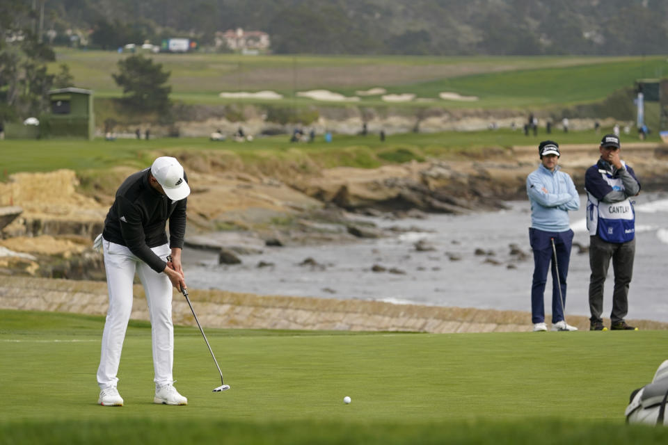 Daniel Berger makes an eagle putt on the 18th green of the Pebble Beach Golf Links during the final round of the AT&T Pebble Beach Pro-Am golf tournament Sunday, Feb. 14, 2021, in Pebble Beach, Calif. Berger won the tournament. Russell Knox, second from right, of Scotland, looks on. (AP Photo/Eric Risberg)