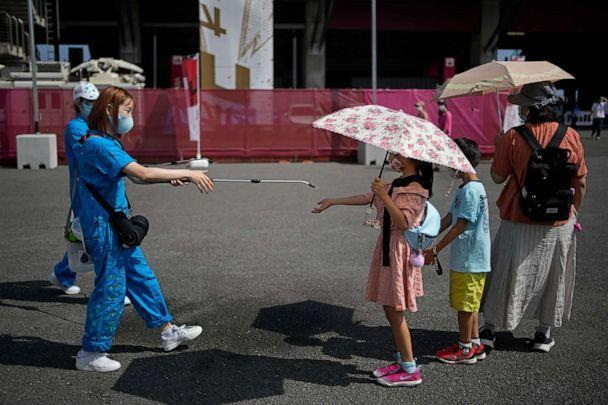 PHOTO: A volunteer sprays water on children as they use umbrellas to beat the heat outside the Fuji International Speedway at the 2020 Summer Olympics, July 25, 2021, in Oyama, Japan. (Christophe Ena/AP Photo)