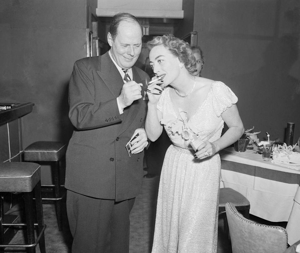 <p>Joan Crawford gets help lighting a cigarette from Sherman Billingsley, the owner of the Stork Club in New York, while attending a party thrown in her honor.</p>