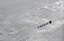 FILE - This March 16, 2009 file photo shows a team driving across Norton Bay just past the Shaktoolik, Alaska checkpoint on the Iditarod Trail Sled Dog Race trail. Fifty-one mushers as of Friday, March 8, 2019, are traveling long stretches between remote village checkpoints with no other company but the dogs pulling their sleds. However, their progress is monitored from several hotel rooms in Anchorage whose 24/7 occupants are the Iditarods electronic eyes and ears. (AP Photo/Al Grillo, File)