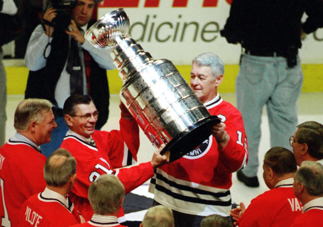 FILE - In this March 17, 1996, file photo, Stan Mikita, second from left, and Ed Lizenberger hoist the Stanley Cup during ceremonies to honor the Chicago Blackhawks' 1961 Stanley Cup championship team before the Blackhawks NHL hockey game against the New York Islanders in Chicago. Mikita, who played for the Blackhawks for 22 seasons, becoming one of the franchise's most revered figures, has died, the Blackhawks announced Tuesday, Aug. 7, 2018. He was 78. (AP Photo/Tim Boyle, File)
