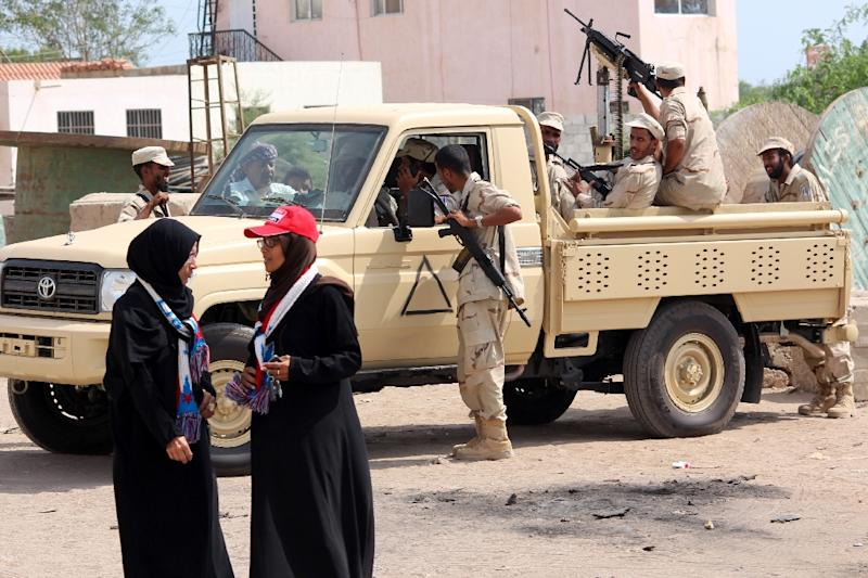 Yemeni women talk in front of government security forces standing guard during the funeral of Aden's governor Jaafar Saad on December 8, 2015 (AFP Photo/Saleh Al-Obeidi)