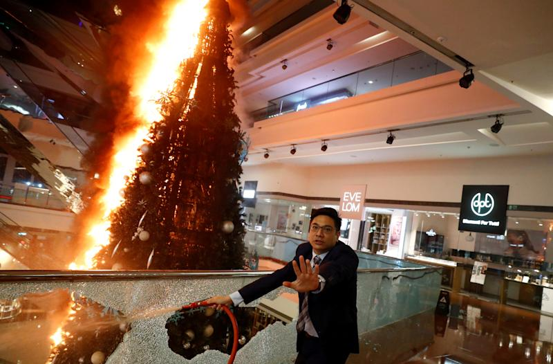 A man reacts as he tries to extinguish a burning Christmas tree at Festival Walk mall in Kowloon Tong, Hong Kong, China November 12, 2019. REUTERS/Thomas Peter TPX IMAGES OF THE DAY