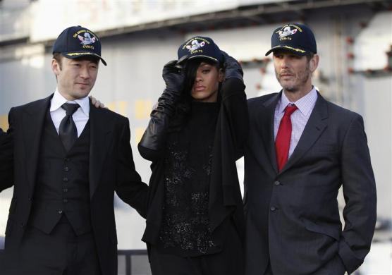 "Rihanna (C), flanked by Tadanobu Asada (L) and U.S. director Peter Berg, wears a cap during a news conference to promote their film ""Battleship"" atop a flight deck of aircraft carrier USS George Washington at Yokosuka port, south of Tokyo April 2, 2012."