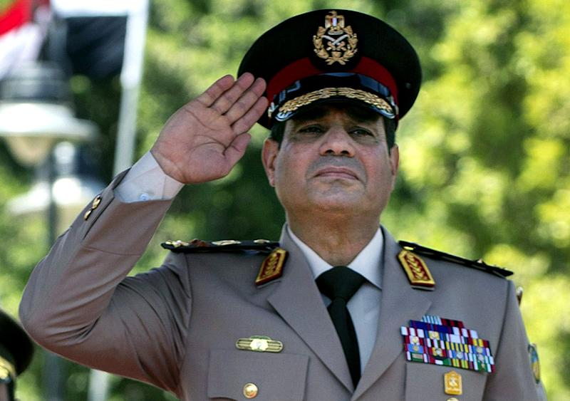 """FILE - In this Wednesday, April 24, 2013 file photo, Egyptian Defense Minister Gen. Abdel-Fattah el-Sissi salutes during an arrival ceremony for U.S. Secretary of Defense Chuck Hagel, at the Ministry of Defense in Cairo. Egypt's military chief on Wednesday called on his countrymen to hold mass demonstrations to voice their support for the army and police to deal with potential """"violence and terrorism,"""" a move that signals a stepped up campaign against supporters of the ousted Islamist president. (AP Photo/Jim Watson, Pool, File)"""