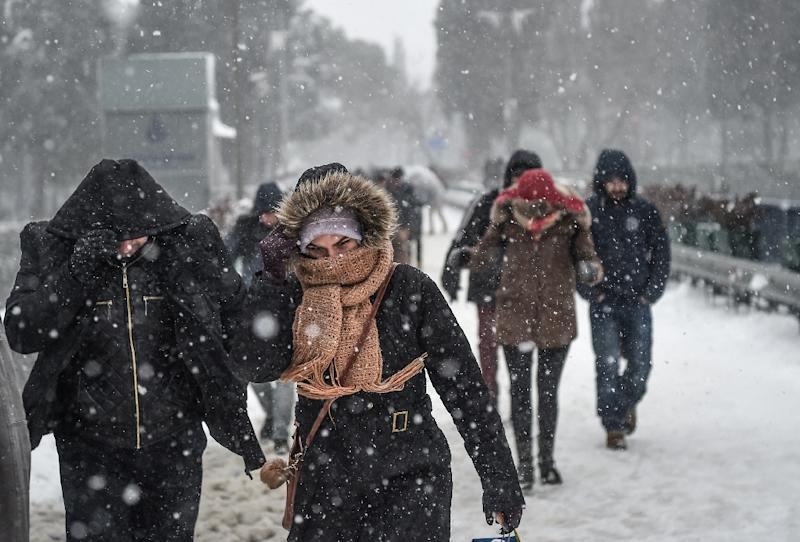 People walk during snowfalls in Istanbul on January 7, 2017