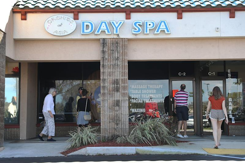People mill around in front of the Orchids of Asia Day Spa after New England Patriots owner Robert Kraft being charged with allegedly soliciting for sex on Feb. 22, 2019 in Jupiter, Florida. Mr. Kraft was caught up in a law enforcement operation in South Florida that netted hundreds of johns over the past two weeks.