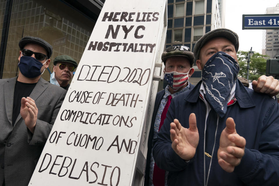 A group of restaurant owners and workers use a mock coffin as a prop while while protesting outside the building which houses New York Gov. Andrew Cuomo's office, Monday, Sept. 28, 2020, in New York. The group is calling for expanded outdoor dining and that indoor dining to be expanded from 25 to 50 percent occupancy. (AP Photo/Mary Altaffer)