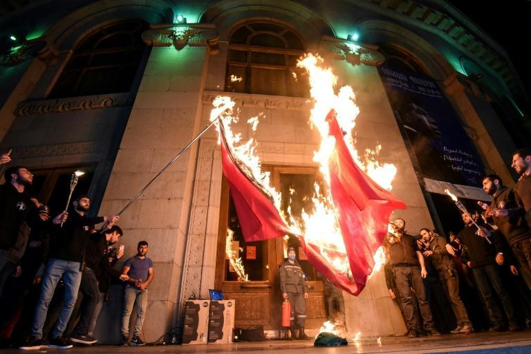 Armenians set fire to the Turkish and Azerbaijani flags in Yerevan on April 23, 2021 during commemorations of what the United States has recognized as a genocide against Armenians by the Ottoman Empire