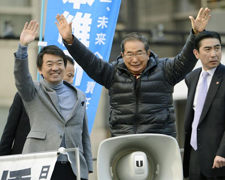 """In this Dec. 9, 2012 photo, Japan Restoration Party leaders, Shintaro Ishihara, center, and Toru Hashimoto, left, wave at their party supporters during their parliamentary elections campaign in Tokyo. The buzz over Japan's parliamentary elections this Sunday, Dec. 16, has been all about """"the third force"""" - a clear sign of the prevailing disenchantment over both the party that ruled for decades after World War II and the rival party that took over in 2009. The new party with the most momentum, and one that could be part of the coalition government, is the Japan Restoration Party, led by former Tokyo Gov. Ishihara and Osaka Mayor Hashimoto, pushing for a more assertive Japan and capable of flexing its military muscle in territorial disputes with China. (AP Photo/Kyodo News) JAPAN OUT, MANDATORY CREDIT, NO LICENSING IN CHINA, FRANCE, HONG KONG, JAPAN AND SOUTH KOREA"""