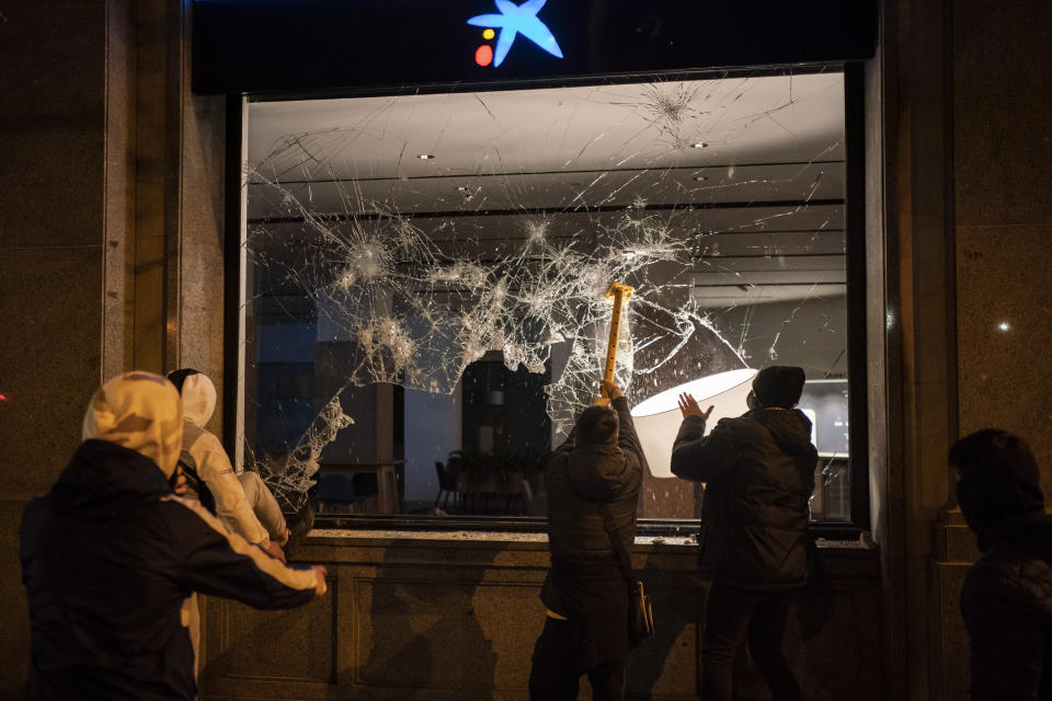 Demonstrators smash the window of a bank following a protest condemning the arrest of rap singer Pablo Hasel in Barcelona, Spain, Thursday, Feb. 18, 2021. The imprisonment of Pablo Hasel for inciting terrorism and refusing to pay a fine after having insulted the country's monarch has triggered a social debate and street protests. (AP Photo/Felipe Dana)