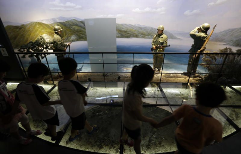 Kindergarten pupils walk by an exhibit dipicting South Korean soldiers during the Korean War at the Korea War Memorial Museum in Seoul, South Korea, Friday, June 7, 2013. North Korea on Friday proposed holding low-level government talks with South Korea this weekend as the rivals look to mend ties that have plunged during recent years amid hardline stances by both countries. (AP Photo/Lee Jin-man)