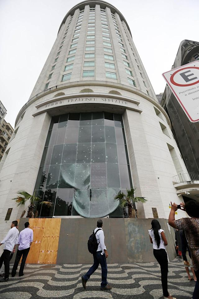 RIO DE JANEIRO, BRAZIL - OCTOBER 30: People walk in front of the front entrance to the office buildingdamaged during protests, which houses the Brazilian oil company OGX, part of Eike Batista's EBX Group Co., on October 30, 2013 in Rio de Janeiro, Brazil. OGX may file for bankruptcy protection as early as today. Batista was Brazil's richest man and the eighth wealthiest in the world but an 18-month collapse has wiped out more than $30 billion of Batistas fortune. (Photo by Mario Tama/Getty Images)