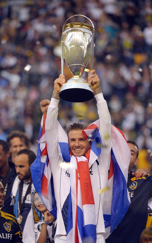 Los Angeles Galaxy midfielder David Beckham holds up their trophy after defeating the the Houston Dynamo 3-1 in the MLS Cup championship soccer game, Saturday, Dec. 1, 2012, in Carson, Calif. AP Photo/Mark J. Terrill)