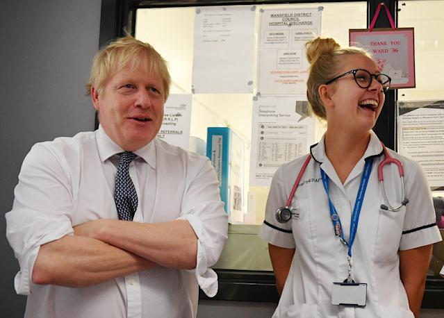 Prime Minister Boris Johnson talks with a physiotherapist as he meets nursing staff during a general election campaign. Photo: Getty Images