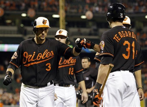 Baltimore Orioles' Ryan Flaherty, left, fist-bumps teammate Taylor Teagarden after hitting a grand slam in the first inning of a baseball game against the Boston Red Sox in Baltimore, Friday, Sept. 28, 2012. (AP Photo/Patrick Semansky)