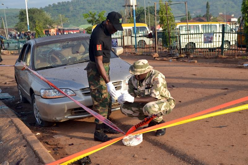 Nigerian bomb experts look for clues in Nyanya, near Abuja, on October 3, 2015, after two bomb blasts ripped through the outskirts of Nigeria's capital Abuja