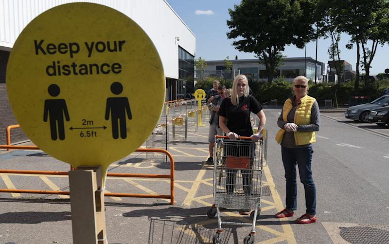 A sign reminds customers at a DIY store in London about observing the two-metre rule - Ming Yeung/Getty Images Europe