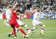 Bahrain's Sayed Ahmed Jaafar is challenged by Iran's Morteza Pouraliganji (R) and Iran's Ehsan Hajisafi during their Asian Cup Group C soccer match at the Rectangular stadium in Melbourne January 11, 2015. REUTERS/Brandon Malone (AUSTRALIA - Tags: SOCCER SPORT)