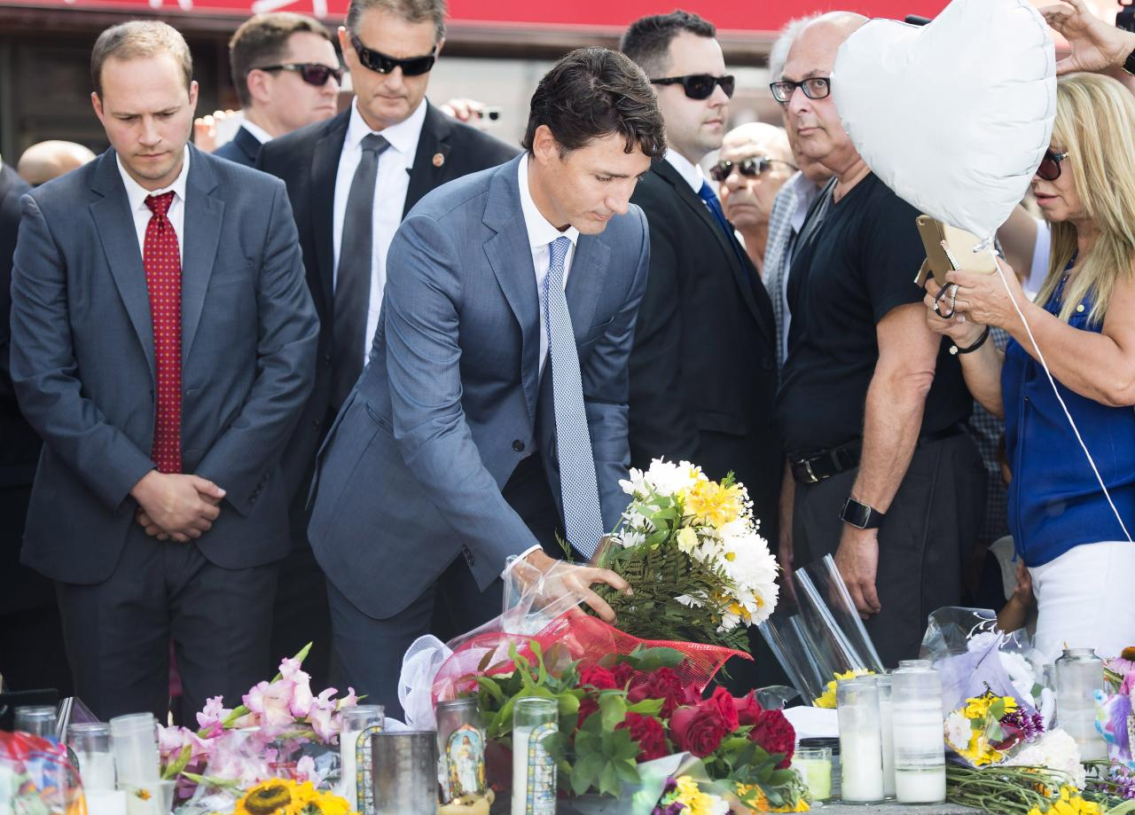 <p>Prime Minister Justin Trudeau, centre places flowers at the fountain at the Alexander the Great Parkette, near where people were gunned down and injured from the recent Danforth shootings in Toronto on Monday, July 30, 2018. Photo from The Canadian Press. </p>
