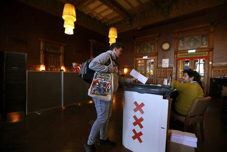 A voter casts their ballot for the European elections at the Central Station in Amsterdam, Netherlands