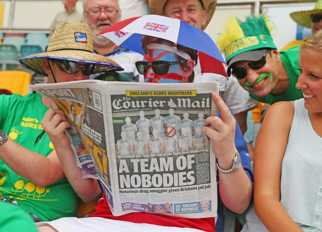 BRISBANE, AUSTRALIA - NOVEMBER 23:  An English supporter reads a copy of the local Courier Mail newspaper during day three of the First Ashes Test match between Australia and England at The Gabba on November 23, 2013 in Brisbane, Australia.  (Photo by Scott Barbour/Getty Images)