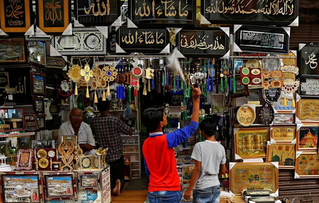 <p>A boy cleans the religious pictures for sale at a shop during Ramadan outside the shrine of Sufi saint Khwaja Moinuddin Chishti in Ajmer, India, May 29, 2017. (Himanshu Sharma/Reuters) </p>
