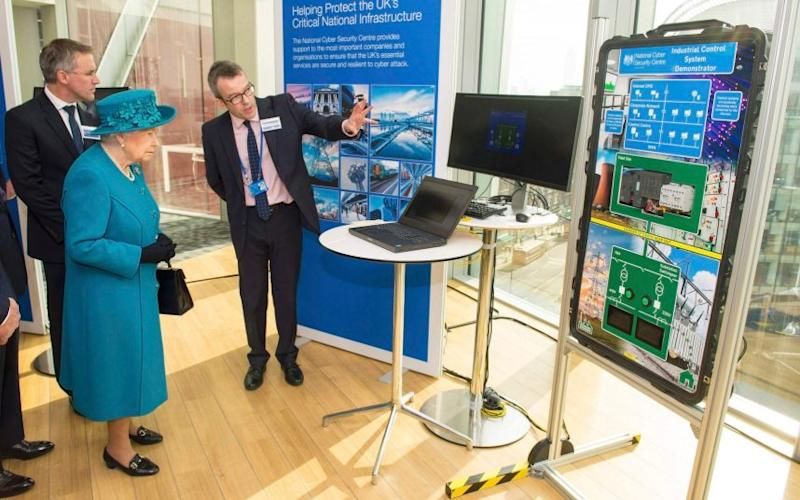 Director of Engagement and Advice, Alex Dewdney, gives Queen Elizabeth a demonstration of how an electricity supply could be subjected to cyber attack, at official opening of the National Cyber Security Centre (NCSC) in London - Credit: POOL