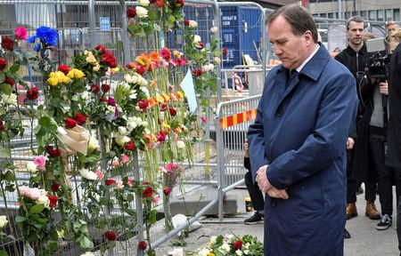 FILE PHOTO: Swedish Prime Minister Stefan Lofven looks at flowers laid for the victims as he visits the crime scene, April 8, 2017, the day after a hijacked beer truck plowed into pedestrians on Drottninggatan and crashed into Ahlens department store, in central Stockholm, Sweden. TT News Agency/Jonas Ekstromer via REUTERS /File Photo