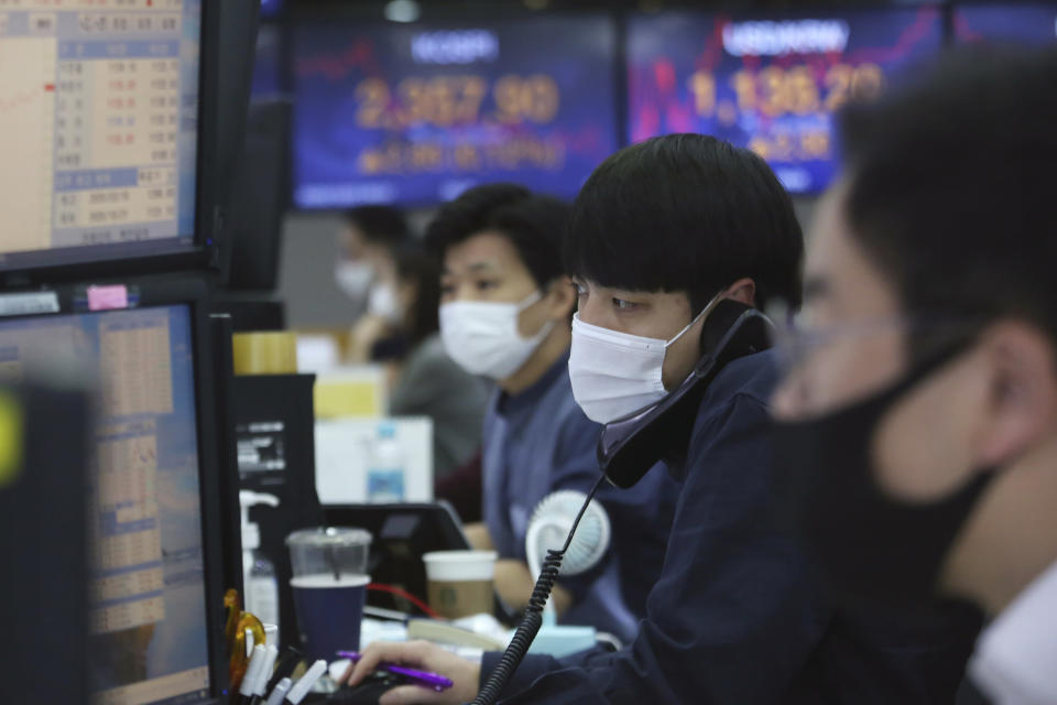 A currency trader talks on the phone at the foreign exchange dealing room of the KEB Hana Bank headquarters in Seoul, South Korea, Friday, Oct. 23, 2020. Shares were mostly higher in Asia on Friday after President Donald Trump and his challenger former Vice President Joe Biden faced off in their second and final debate before the Nov. 3 election. (AP Photo/Ahn Young-joon)