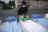 A demonstrator places a Brazil national flag on a mattress symbolizing COVID-19 victims, during a protest against the Government's handling of the COVID-19 pandemic, organized by the Rio de Paz NGO, in front of the Ronaldo Gazolla hospital in Rio de Janeiro, Brazil, Wednesday, March 24, 2021. (AP Photo/Silvia Izquierdo)