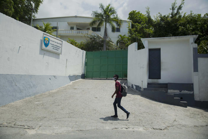 A pedestrian walks past the Catholic University of Notre Dame of Haiti in the Croix-des-Bouquets neighborhood of Port-au-Prince, Haiti, Wednesday, April 21, 2021. Catholic institutions including schools and universities closed Wednesday across Haiti as part of a three-day protest to demand the release of nine people including five priests and two nuns kidnapped more than a week ago amid a spike in violence the government is struggling to control. (AP Photo Joseph Odelyn)
