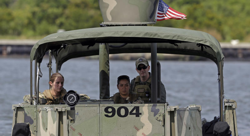 In this Aug. 13, 2013, photo U.S. Navy Master-at-Arms Third Class Danielle Hinchliff, left, and Master-at-Arms Third Class Anna Schnatzmeyer, both of Coastal Riverine Squadron 2, train under the watchful eye of instructor Boatswain's Mate Second Class Christopher Johnson while training on a Riverine Assault Boat as they participate in a U.S. Navy Riverine Crewman Course at the Center for Security Forces Learning Site at Camp Lejeune, N.C. This is the first time female participants have received this training as women begin to take on combat roles in the military. (AP Photo/Gerry Broome)