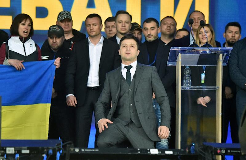 Comedian Zelensky takes a knee during the debate (AFP Photo/Sergei SUPINSKY)