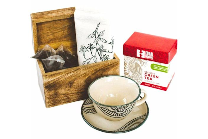 """<p>If mom loves tea, gift her this set of a hand-stamped tea towel, a glass teacup and saucer, and loose leaf green tea.</p><p><a class=""""link rapid-noclick-resp"""" href=""""https://go.redirectingat.com?id=74968X1596630&url=https%3A%2F%2Fshop.globein.com%2Fcollections%2Fartisan-boxes%2Fproducts%2Ftea-time-box&sref=https%3A%2F%2Fwww.countryliving.com%2Fshopping%2Fgifts%2Fg19663932%2Fmothers-day-gift-baskets%2F"""" rel=""""nofollow noopener"""" target=""""_blank"""" data-ylk=""""slk:SHOP NOW"""">SHOP NOW </a></p>"""