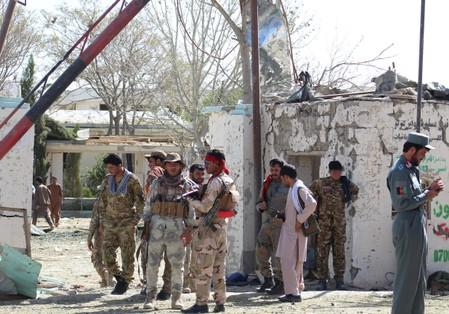 sAfghan security forces stand at the site of a car bomb attack in Qalat, capital of Zabul province
