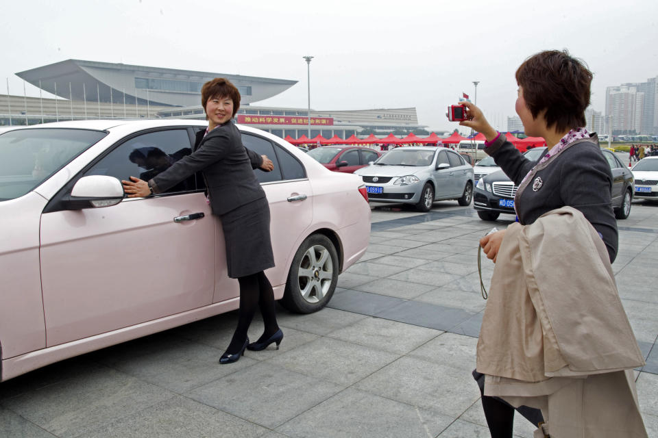 Salespersons pose for pictures in front of a pink sedan, an award for the best sales team, during the Mary Kay China Leadership Conference on February 20, 2011, in China. (Photo by China Photos/Getty Images)