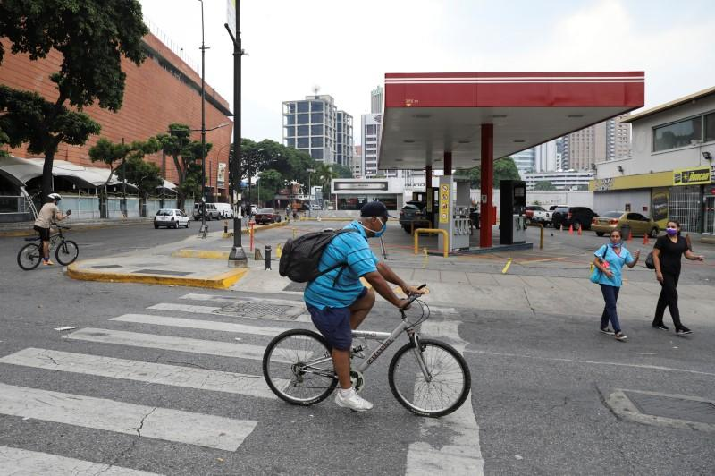 People riding bicycles pass in front of a closed gas station in Caracas