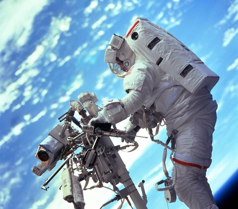 STS103-701-047 (19-27 December 1999) --- Astronaut Steven L. Smith, payload commander, retrieves a power tool while standing on the mobile foot restraint at the end of the remote manipulator system (RMS). Many of the tools required to service the Hubble Space Telescope are stored on the handrail attached to the RMS visible in the photograph.