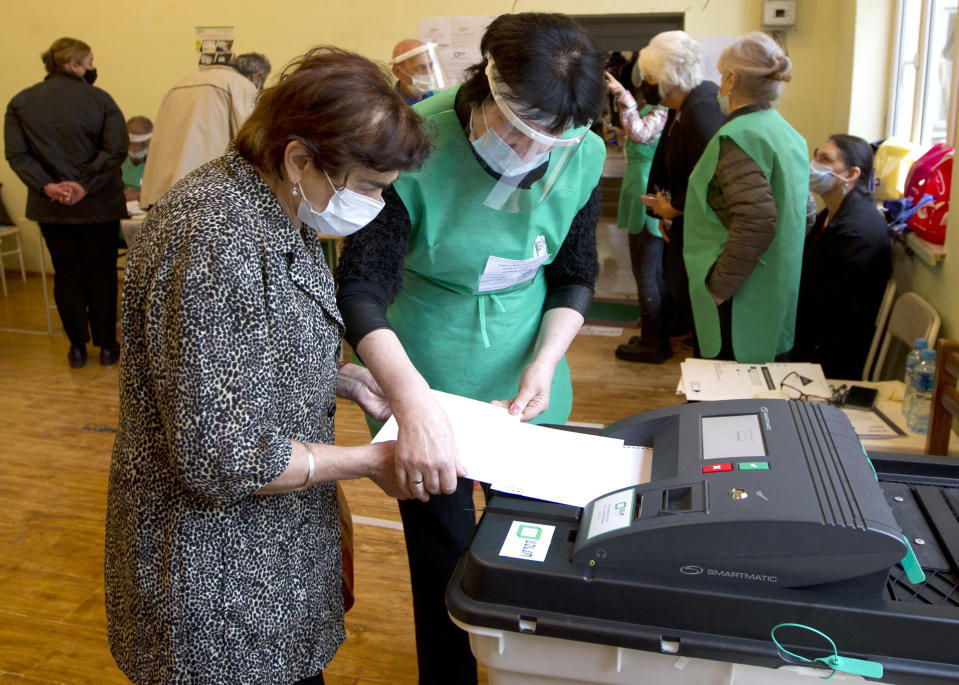 A member of an election commission helps to a woman to cast her ballot at a polling station during national municipal elections in Tbilisi, Georgia, Saturday, Oct. 2, 2021. Former President Mikheil Saakashvili was arrested after returning to Georgia, the government said Friday, a move that came as the ex-leader sought to mobilize supporters ahead of the national municipal elections seen as critical to the country's political makeup. The elections started Saturday. (AP Photo/Shakh Aivazov)