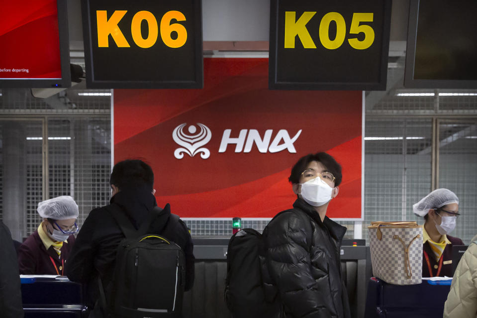 Travelers wearing face masks to protect against the spread of the coronavirus wait in line at the Hainan Airlines check-in counters at Beijing Capital International Airport in Beijing, Friday, March 6, 2020. Hainan Airlines' owner HNA Group, a debt-burdened Chinese airline operator that faced opposition in Washington to its attempt to buy a Wall Street hedge fund during a costly global acquisition spree, says its creditors have asked a court to declare the company bankrupt. (AP Photo/Mark Schiefelbein)