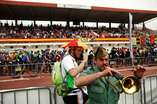 "Spanish runner Carlos Garcia, 26, uses his phone while a Spanish legionnaire plays a trumpet during the start of the cycling category during the XXI 101km international competition, where participants run a track through the ""Serrania de Ronda"" (Ronda Mountain Range) in less than 24 hours, in Ronda, southern Spain, May 12, 2018. Picture taken May 12, 2018. REUTERS/Jon Nazca"