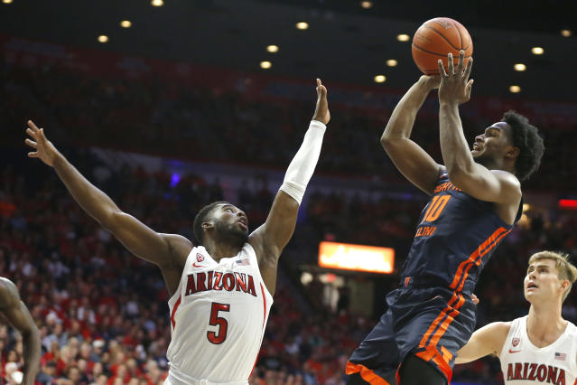 Illinois guard Andres Feliz (10) shoots over Arizona guard Max Hazzard (5) during the first half of an NCAA college basketball game Sunday, Nov. 10, 2019, in Tucson, Ariz. (AP Photo/Rick Scuteri)