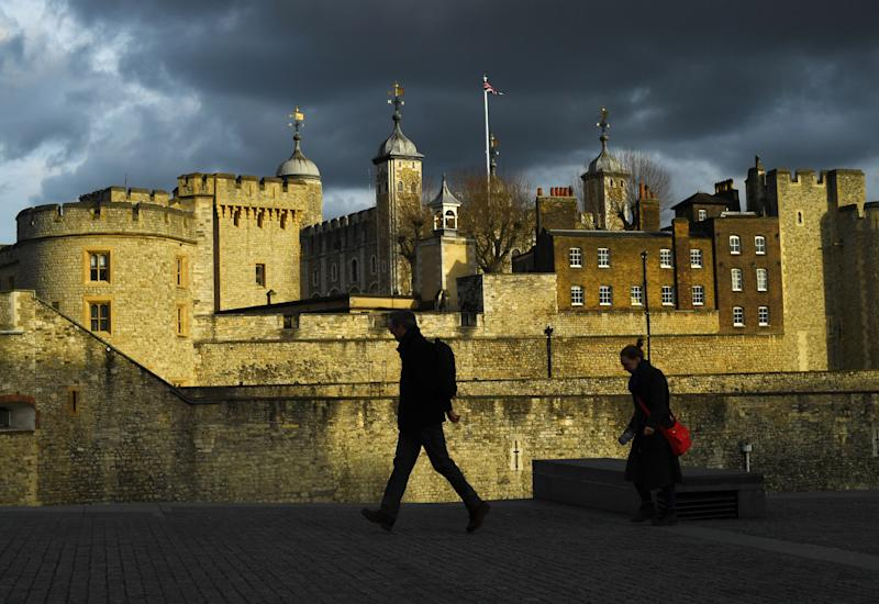 "People walk outside the Tower of London as it closes its doors to tourists and the public after the British government issued advice to maintain ""social distancing"" as a means of responding to the global coronavirus disease (COVID-19) outbreak, in London, Britain, March 20, 2020. REUTERS/Dylan Martinez"