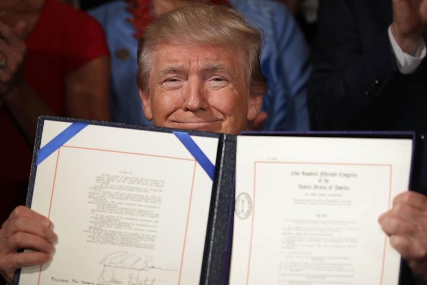 President Trump holds the Accountability and Whistleblower Protection Act of 2017 after signing it during a ceremony in the East Room of the White House June 23, 2017 in Washington, DC.