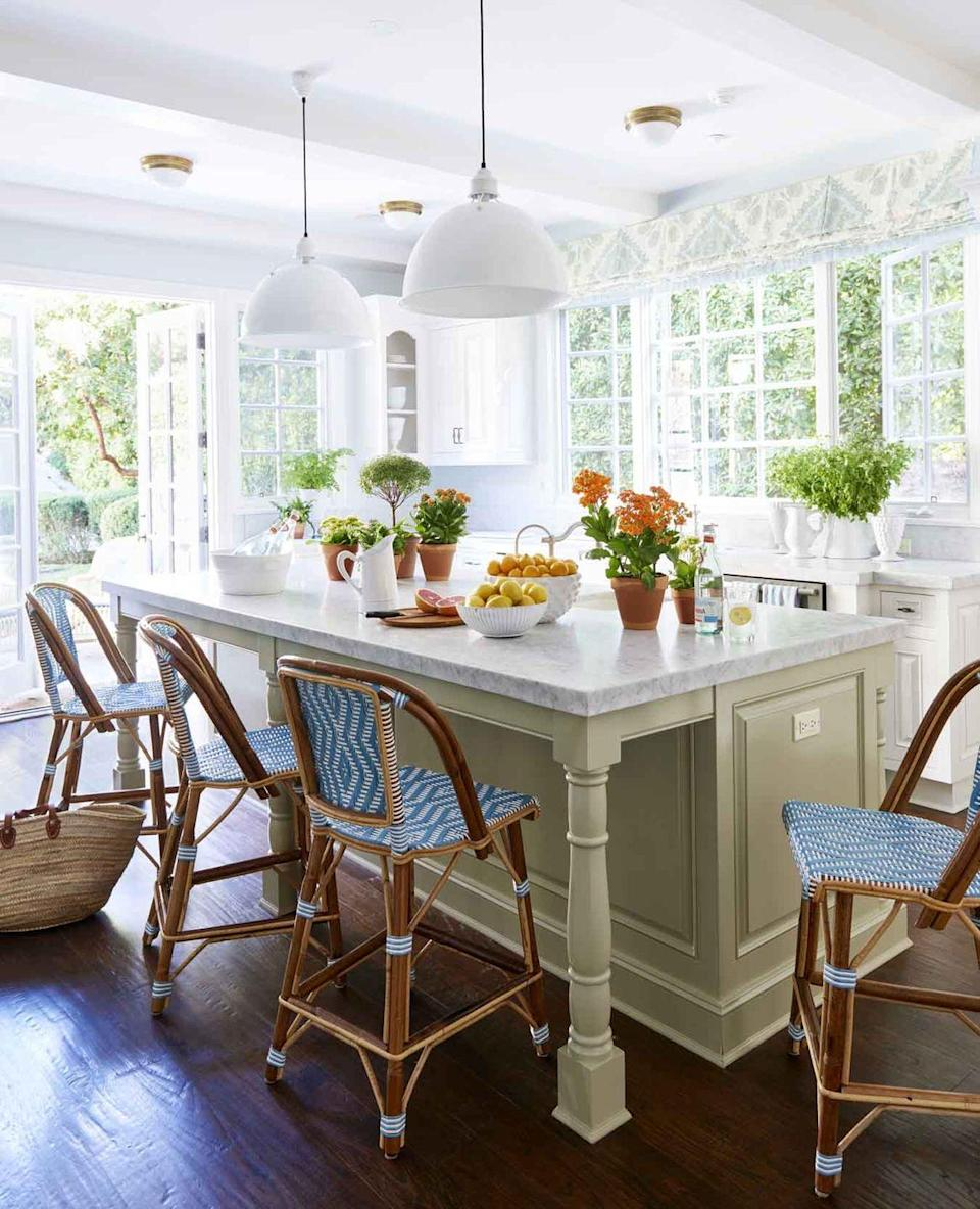 <p>With white walls, cabinets, lighting, and loads of natural light from surrounding windows, Designer Mark D. Sikes brought in just the right amount of color with blue-and-white French bistro stools, a mossy-green island, and patterned Roman shades.</p>