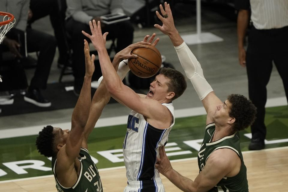 Orlando Magic's Moritz Wagner is fouled as he shoots between Milwaukee Bucks' Giannis Antetokounmpo and Brook Lopez during the second half of an NBA basketball game Tuesday, May 11, 2021, in Milwaukee. (AP Photo/Morry Gash)